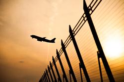 夕焼け空を飛ぶ飛行機の画像