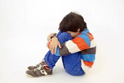 膝を抱える少年の画像