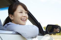 車の窓から顔を出す女性の画像