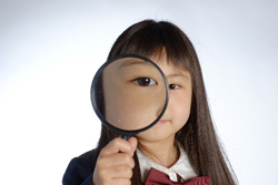 虫眼鏡を持つ少女の画像