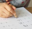 テスト用紙に書き込む子供の手の画像