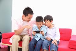 ゲームをする父親と子供達の画像