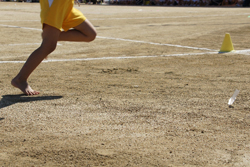 グラウンドを走る陸上選手の足の画像