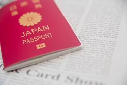 パスポートと英字新聞の画像