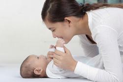 赤ちゃんをあやす母親の画像