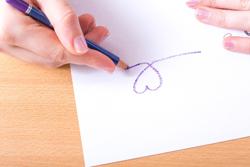 紙にハートを書く手の画像