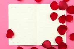 散らばったバラの花びらとノートの画像